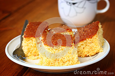 Lemon cake and cup of coffee on wooden table