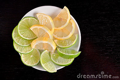 Lemon and lime slices on black wood table.