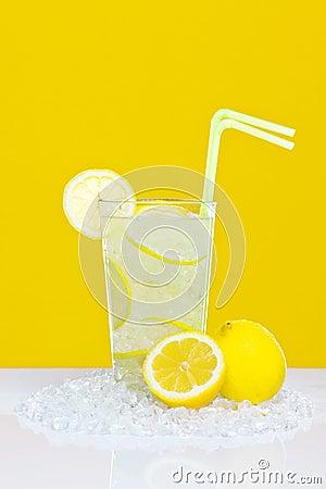 Lemonade in glass yellow background