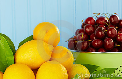 Lemons And Ripe Red Cherries In Green Colander