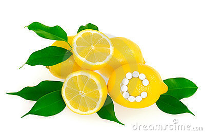 Lemons with vitamin c pills over white background