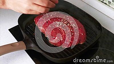 Lent mouvement de la main de l'homme Saupoudrée de sel sur du steak de boeuf grillé sur un plateau de grillades clips vidéos