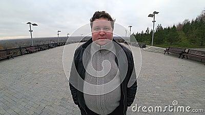 Lente de grande ângulo: jovem gordo em pé na paisagem urbana e olhando para a câmera com confiança vídeos de arquivo