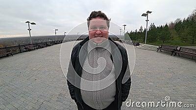 Lente de grande ângulo: jovem gordo em pé na paisagem urbana, olhando para a câmera e sorrindo video estoque