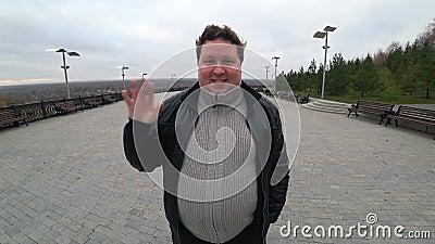 Lente de grande ângulo: jovem gordo está cumprimentando alguém Um homem está balançando a mão filme
