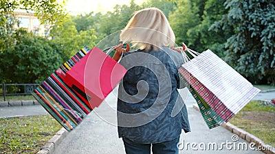 Lento movimento di bionda matura che gira fuori a tenere i sacchetti della spesa con divertimento stock footage
