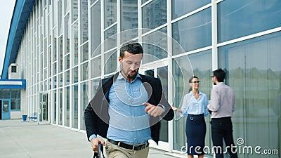 Lento movimiento de un guapo joven corriendo con un maletín a lo largo del edificio de oficinas almacen de metraje de vídeo