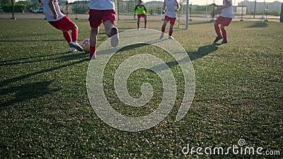 Les écoliers en uniforme de football but de score faible angle de tir banque de vidéos