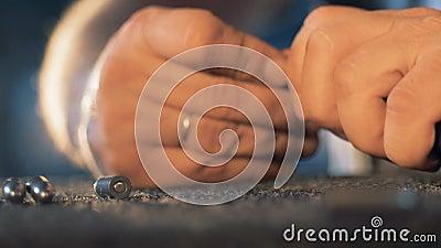 Les balles obtiennent chargées dans la cartouche de l'arme à feu par les mains masculines dans une fin  clips vidéos
