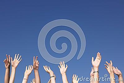 Les bras ont augmenté contre le ciel bleu