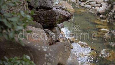 Les coulées d'eau pure de montagne coulent au-dessus des pierres de la cascade banque de vidéos