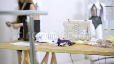 Les coupes d'ouvrière couturière filètent du tissu de dentelle sur les machines à coudre dans l'atelier clips vidéos