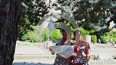 Les dames lisent la brochure de visite guidée et pointent vers la destination banque de vidéos