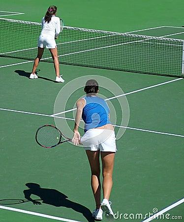 Les doubles de tennis servent et tirent une volée