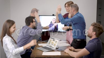 Les employés de bureau communiquent avec le patron par appel vidéo, se réjouissent, célèbrent une victoire dans la salle de réuni banque de vidéos