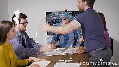 Les employés de bureau se rencontrent et discutent dans la salle de conférence, deux hommes se disputent et jettent des documents banque de vidéos