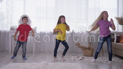 Les enfants dansant en t-shirts multicolores s'amusent sur le dos de vitres vives dans une pièce blanche pendant les vacances à clips vidéos