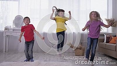 Les enfants dansent et sautent dans des t-shirts multicolores contre une fenêtre lumineuse dans une pièce blanche pendant les vac clips vidéos