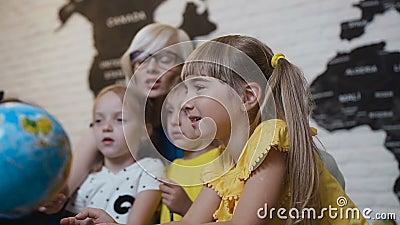 Les enfants mignons avec le professeur s'assied à la table dans la salle de classe de la géographie et étudie curieusement le glo banque de vidéos