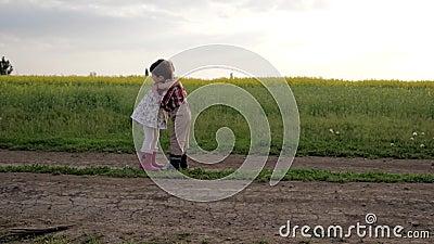 Les enfants mignons s'étreignant, rencontrant des amis, courant autour de la route de champ, mouvement lent, garçon et fille sont banque de vidéos
