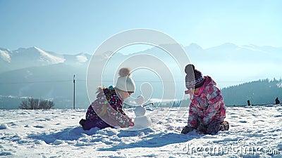 Les enfants outwear dedans faire le petit bonhomme de neige tout en jouant sur le champ neigeux au soleil avec des montagnes sur  banque de vidéos