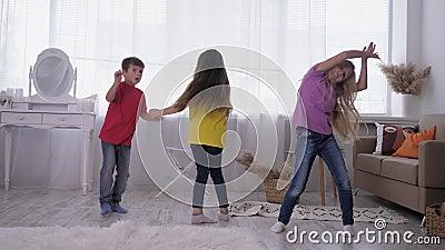 Les enfants qui dansent dans des t-shirts multicolores s'amusent sur le dos d'une fenêtre lumineuse dans une pièce blanche pendan banque de vidéos