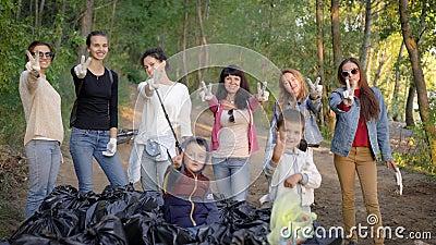 Les femmes et les enfants montrent le signe de la victoire en posant des doigts près des déchets collectés dans la zone boisée, h banque de vidéos