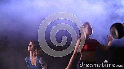 Les femmes sexy sportives, faisant la forme physique s'exerce avec des pondérations, la nuit, dans la fumée légère, brouillard, à clips vidéos
