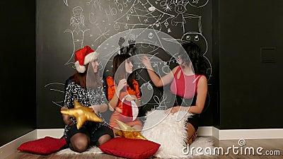 Les filles dans des chapeaux de Santa jouent avec des oreillers banque de vidéos