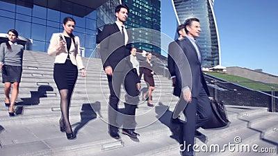 Les gens d'affaires descendent des escaliers