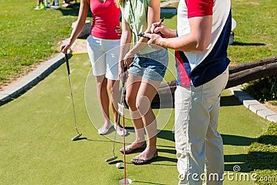 Les gens jouant au golf miniature à l extérieur