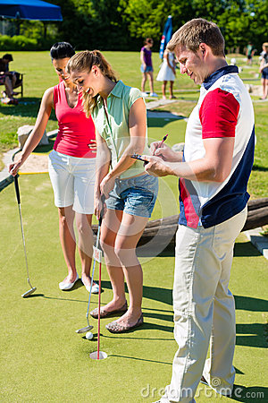 Les gens jouant le golf miniature dehors