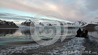 Les gens nagent sur le canot sur l'eau de l'océan arctique dans le Svalbard clips vidéos