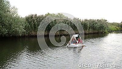 Les gens ramant dans un bateau en caoutchouc de canot le long à la rivière de Havel Reed et saule essaye le rivage clips vidéos