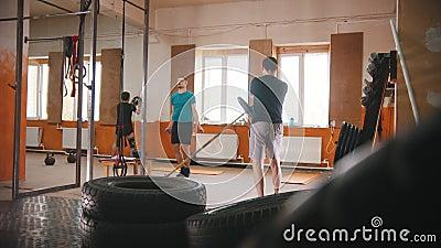 Les hommes s'entraînent dans la petite salle de fitness banque de vidéos