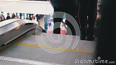 Les jambes des personnes se déplaçant dans un ascenseur à escalator dans le centre commercial Les pieds dans l'escalator du centr banque de vidéos