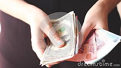 Les mains d'une femme voyageuse racontent son argent liquide dans différentes monnaies banque de vidéos