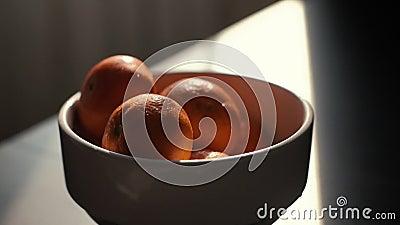 Les mains d'une jeune femme ont mis des mandarines dans le plat dans le mouvement lent clips vidéos