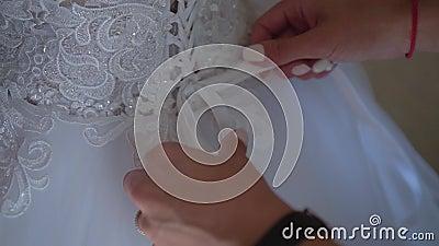 Les mains des femmes ont attaché derrière la corde sur la robe Les honoraires de la jeune mariée banque de vidéos