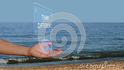 Les mains sur le texte d'hologramme de prise de plage pensent différent banque de vidéos
