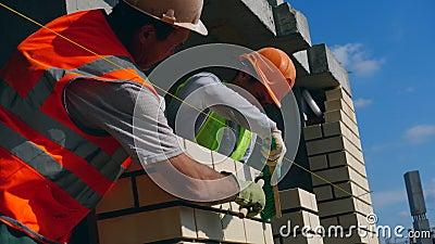 Les ouvriers brossent un mur en brique nouvellement construit banque de vidéos