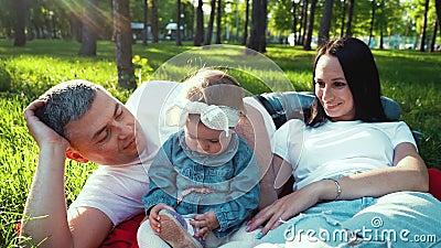Les parents heureux regardent le bébé jouant avec sa chaussure sur l'herbe verte en parc banque de vidéos