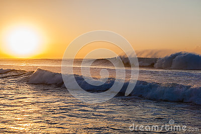 Les ressacs lavent au jet le lever de soleil