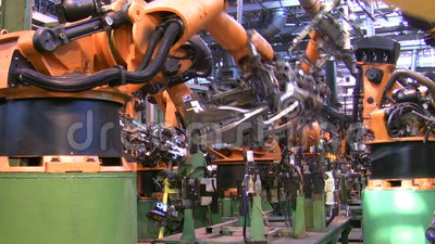 Les robots soudent des pièces de voiture dans la chaîne de production à l'usine