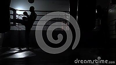 Les types dans les gants bat une poire, à l'arrière-plan dans l'anneau il y a une boxe d'entraînement des kickboxers Mouvement le clips vidéos