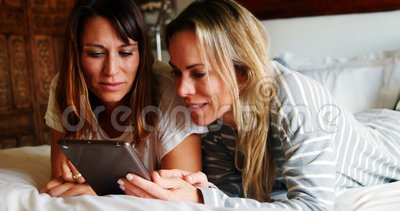 Lesbisch paar die digitale tablet op bed 4k gebruiken stock video