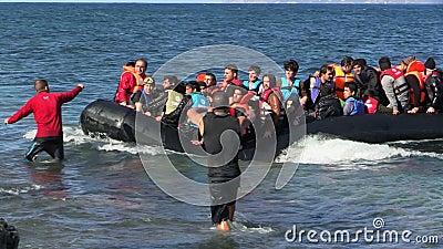 LESVOS, ГРЕЦИЯ - 2-ОЕ НОЯБРЯ 2015: Беженцы в резиновой шлюпке плавают для того чтобы подпирать от Турции