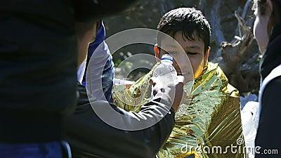 LESVOS, ГРЕЦИЯ - 5-ОЕ НОЯБРЯ 2015: Замороженный беженец мальчика в грея фольге