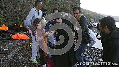 LESVOS, GRECIA - 5 NOVEMBRE 2015: I volontari aiutano la donna del rifugiato a andare sulla riva