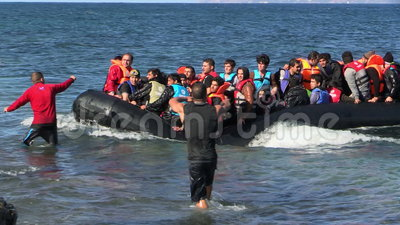 LESVOS, GREECE - NOV 2, 2015: Refugees in a rubber dinghy swim to shore from Turkey. On the sea a big waves